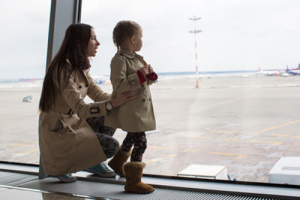 Mother and little daughter looking out the window at airport ter
